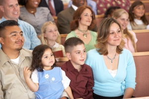 People sitting on pews in church, smiling